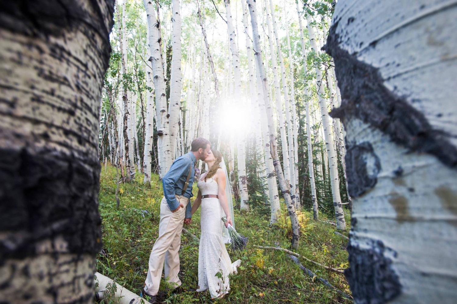 bride and groom kiss under aspens