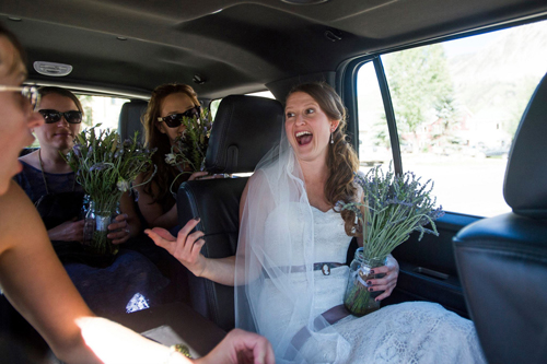 bride and bridesmaids ride in car holding bouquets