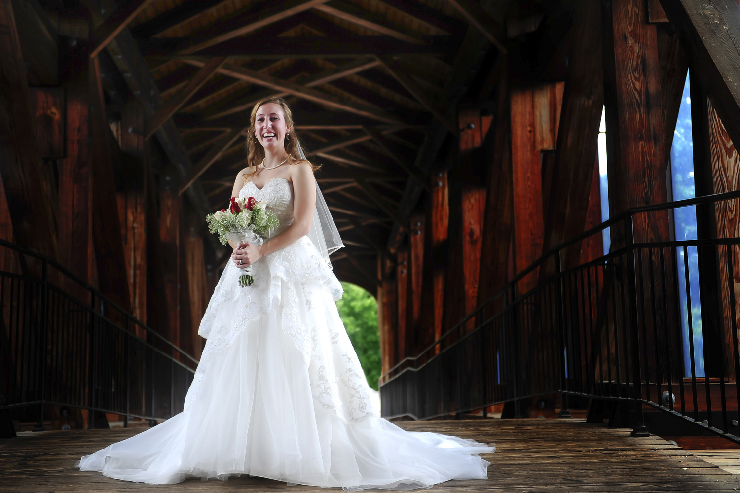 bride standing on covered bridge