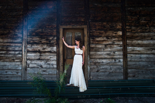 bride standing against wooden backdrop