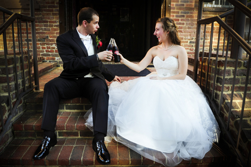 bride and groom sit on stairs and toast with a coke