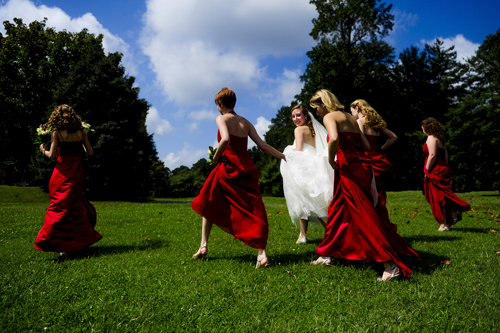 bride walking across grass with bridesmaids in red