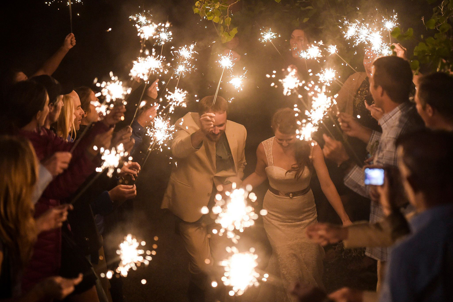 couple exits wedding through glowing sparklers