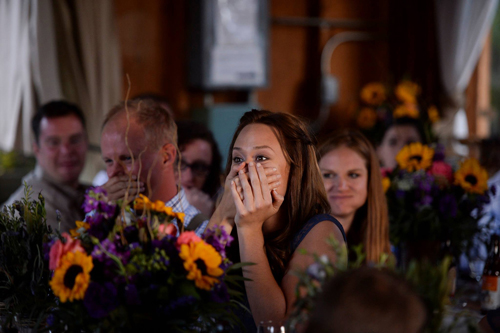woman covering mouth in surprise at wedding